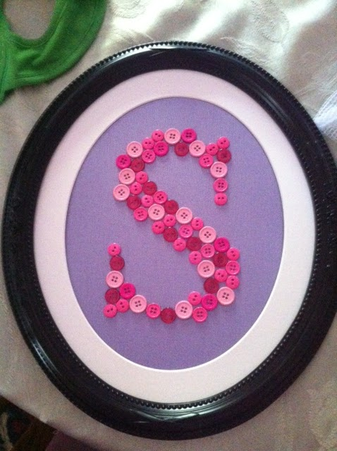 button letter S made in shades of pink on a purple background in a dark oval frame with a white matte