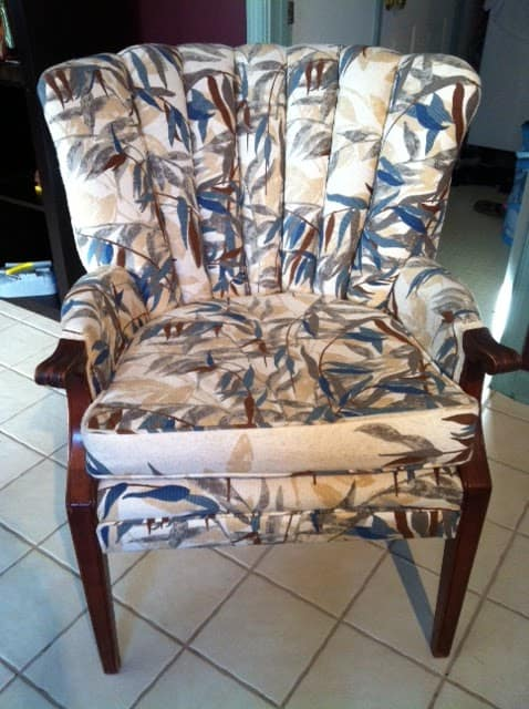 channel backed chair with brown wood arms and feet pattern on fabric is shades of tan, deep blue green and brown in palm-ish like leaf-y pattern on a tile floor