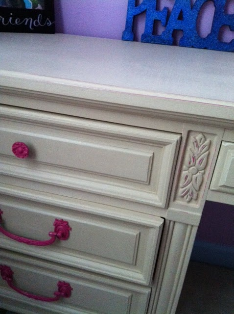 close up of trim work on finished painted desk. handles and undercoat of berry pink and top coat of light tan color distressed to reveal the berry color