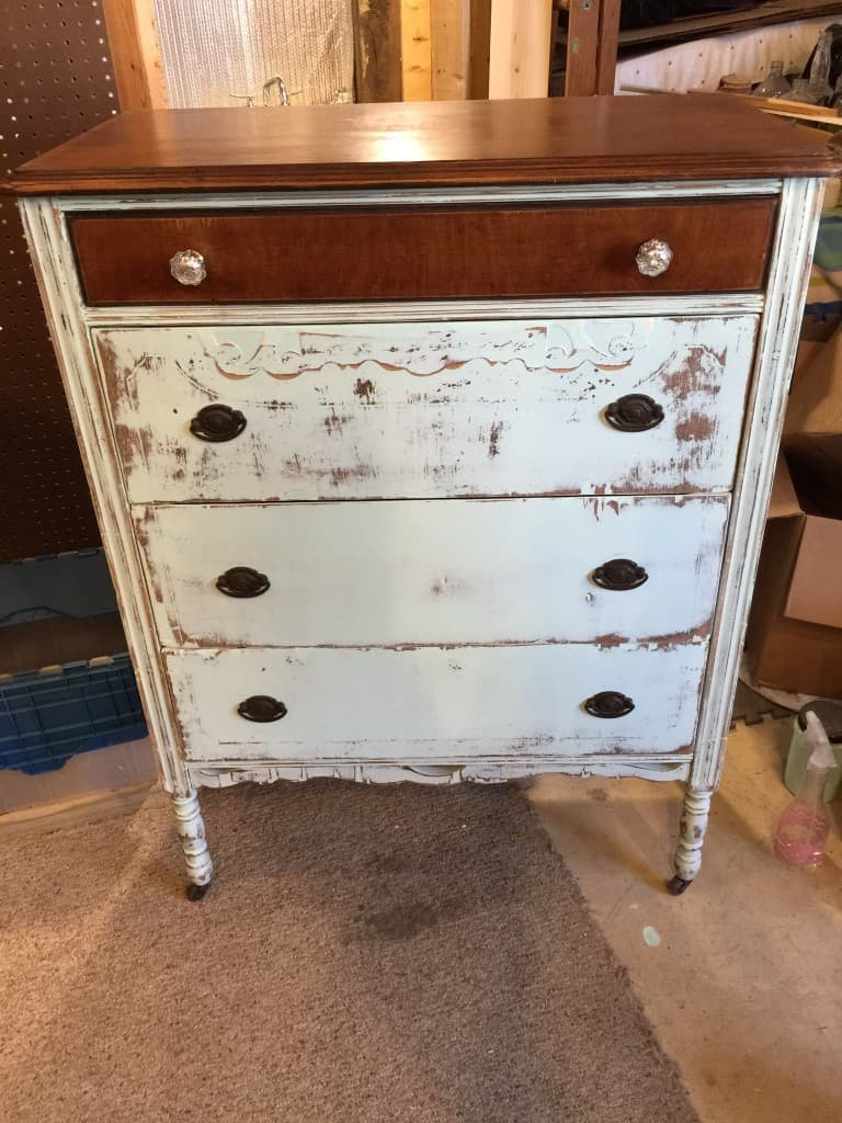 Antique dresser with heavy distressing and glass knobs on top drawer in workshop setting