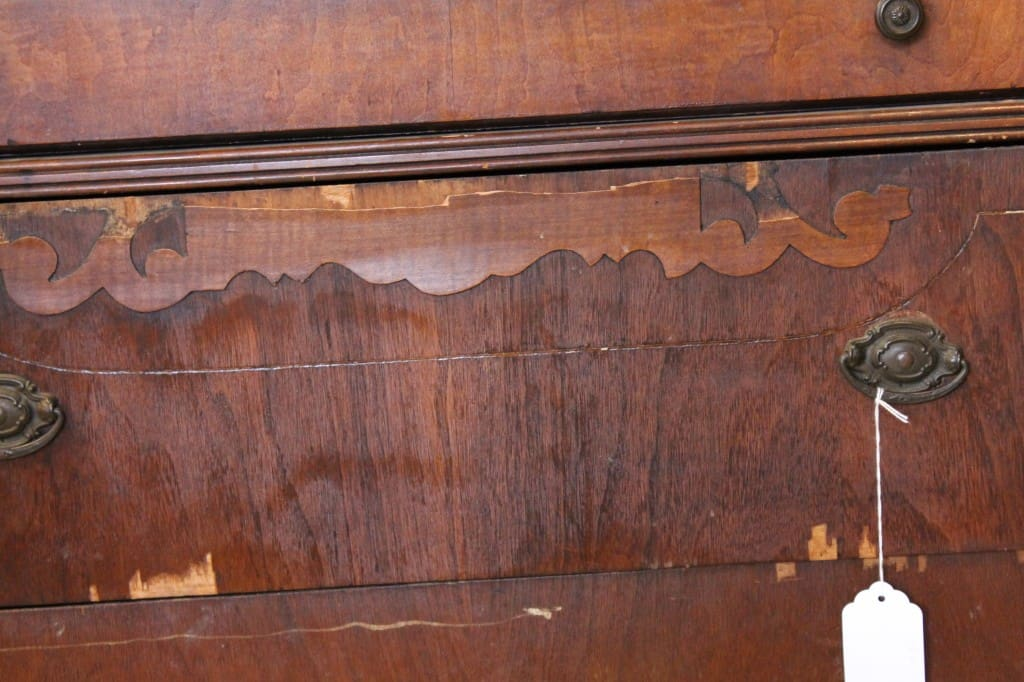 close up of antique dresser front with peeling veneer