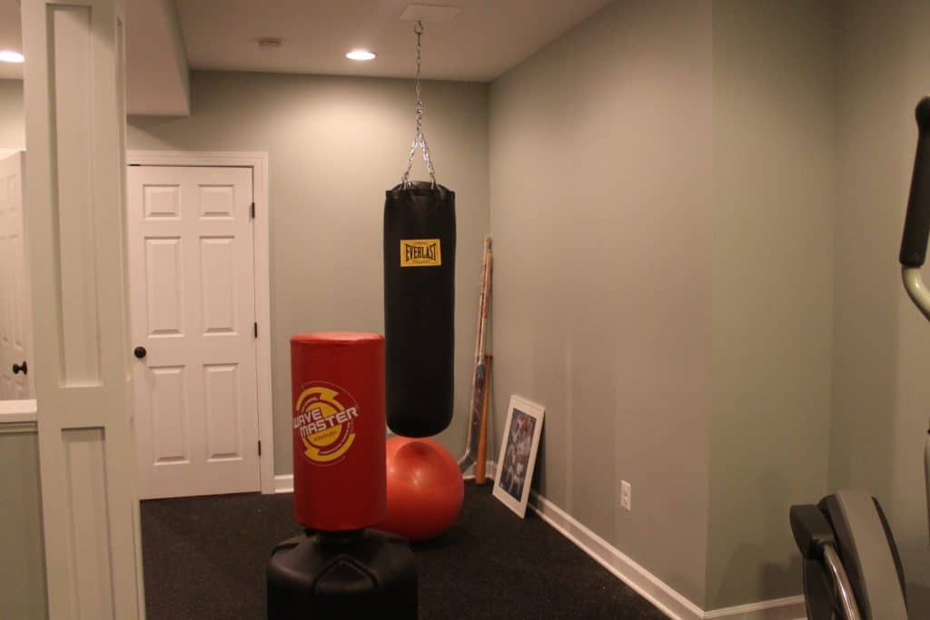 home gym before punching bag hanging in center of image with floor punching dummy next to it. hockey sticks in corner with exercise ball and framed sports poster leaning against the wall.