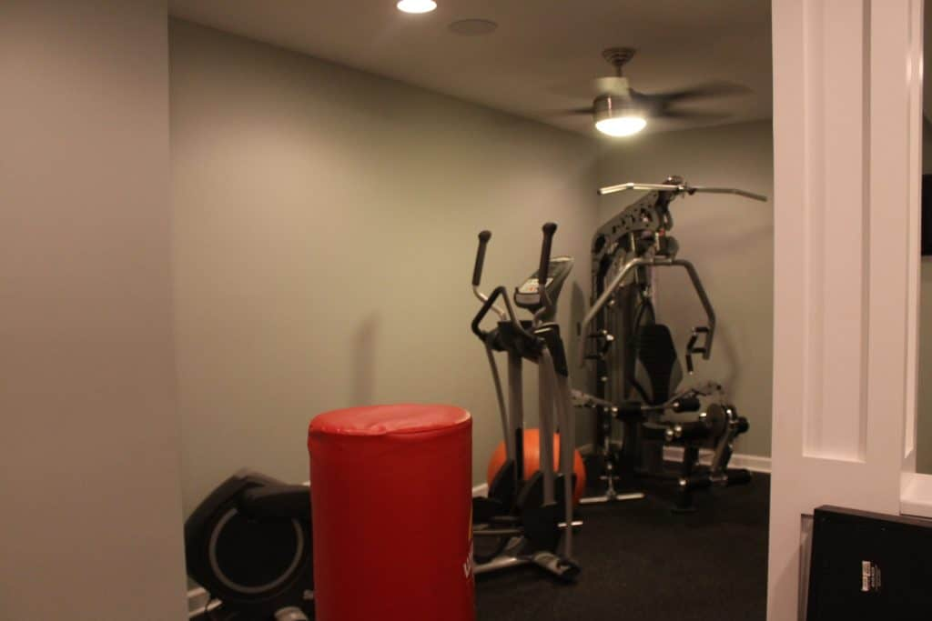 sxs home gym before exercise equipment in background on side of gym wall.