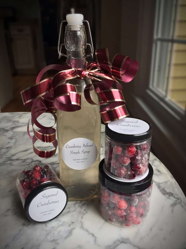sweet and simple holiday gift showing a bottle of cranberry infused simple syrup with jars of sugared cranberries around it on a marble table top.