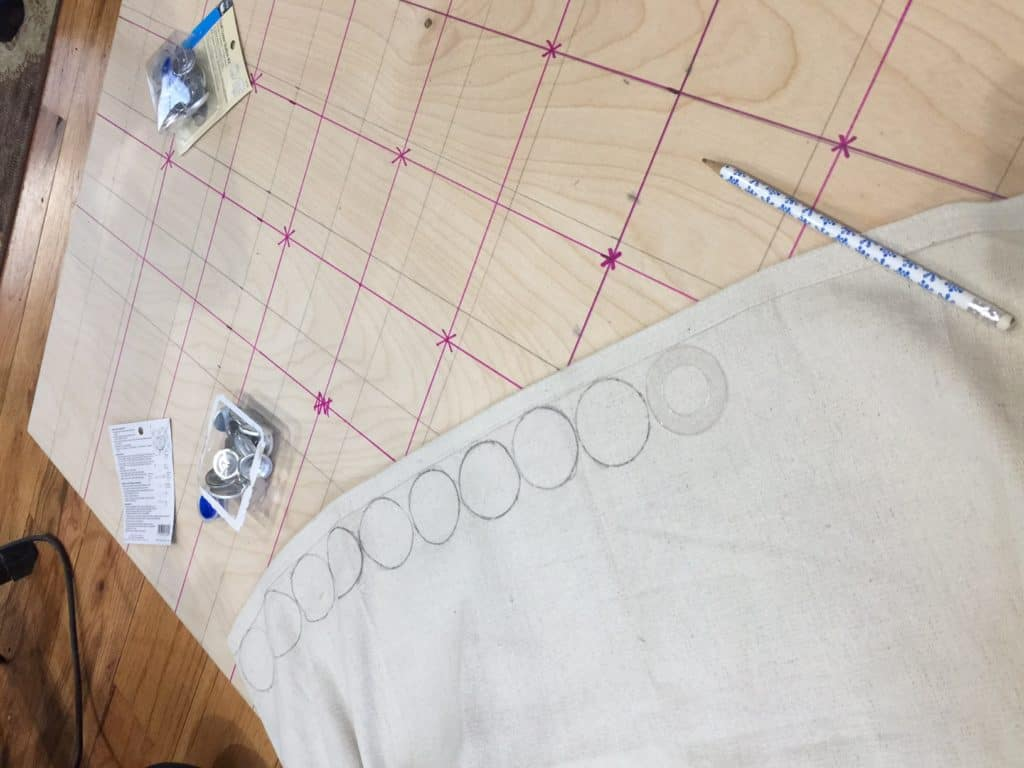 rear of plywood with lines and fabric with circles for covered buttons
