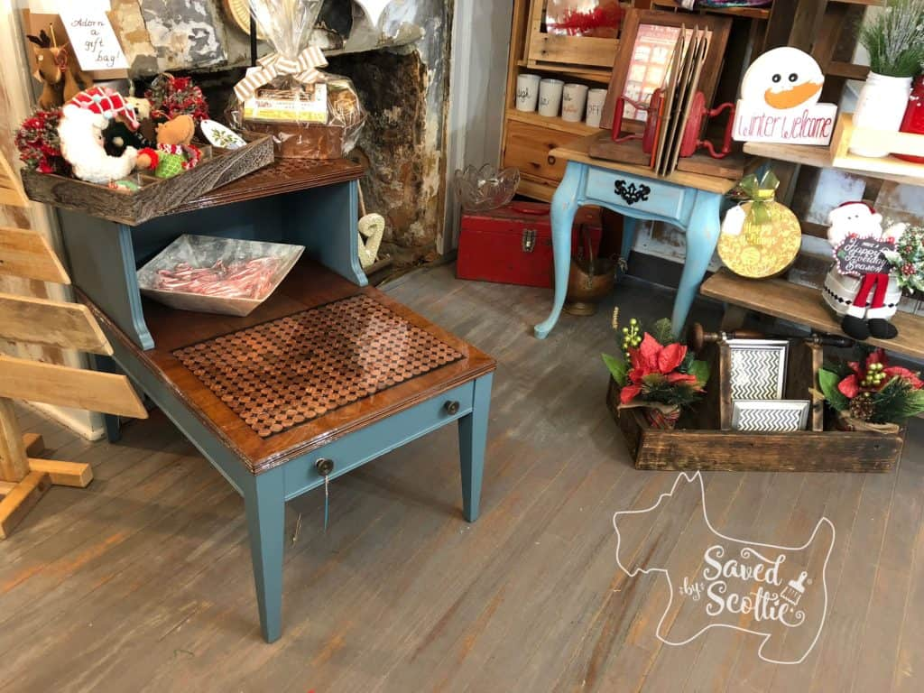 the finished penny table in a retail setting with holidays decorations surrounding it.