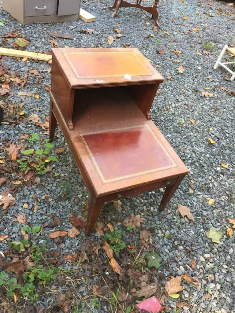 old double layer wooden side table sitting outside on gravel