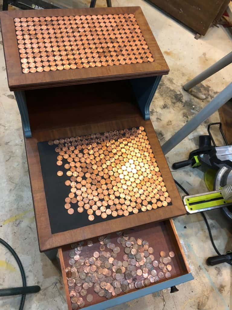 the top section of the table is complete and the bottom section has pennies both lined up and scattered about to see how they all fit before glueing.