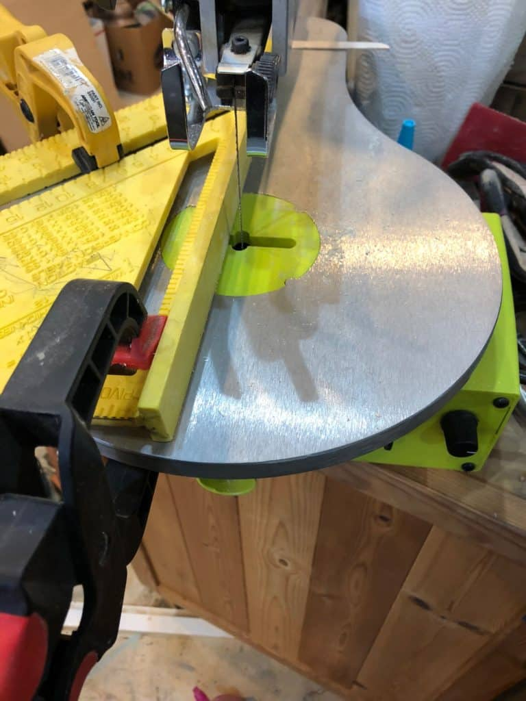 a close up of a speed square clamped to the work surface of a scroll saw to make a jig to cut thin slices of wood.
