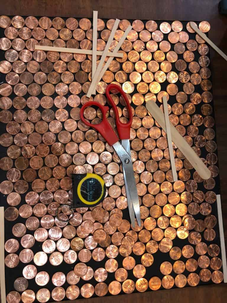 a picture of pennies, scissors, a tape measure and popsicle stick tools used to make the pennies fit properly in the bottom section of the side table.