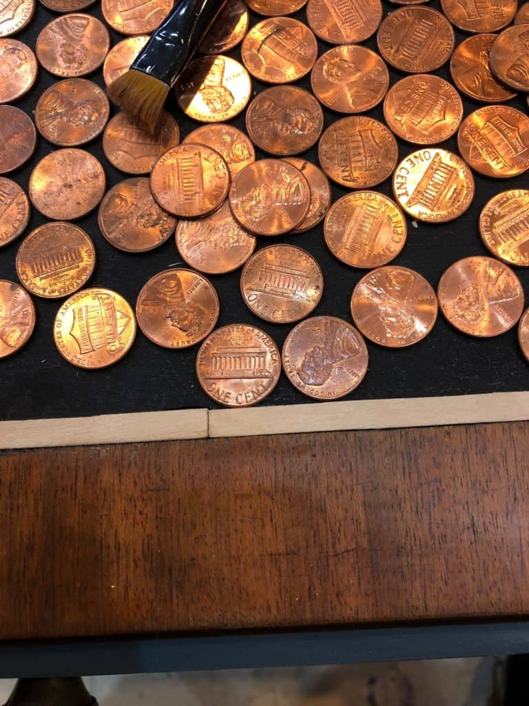 a close up of pennies and thin popsicle sticks buttjoined together with a noticeable seam.