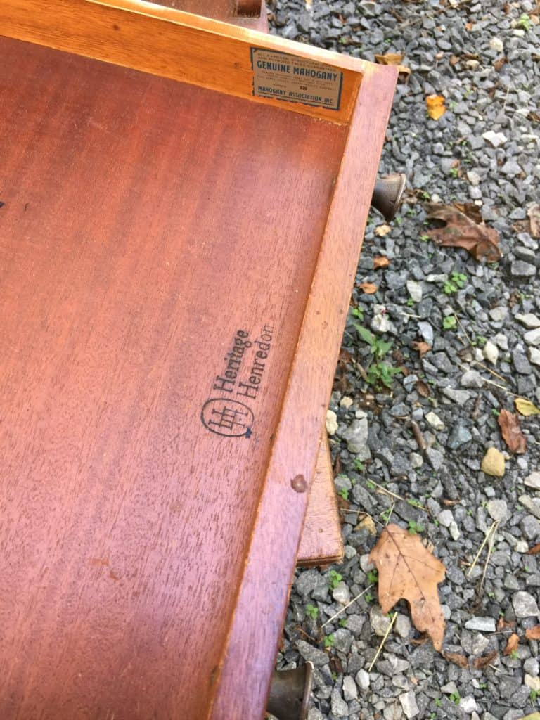 inside the drawer of the side table. A brand is burned into the wood that reads Heritage Henredon with a double H logo