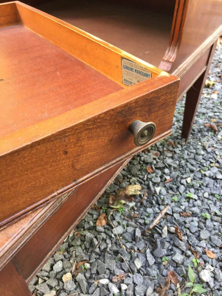 on the side of the drawer is an original sticker that states the wood is genuine mahogany