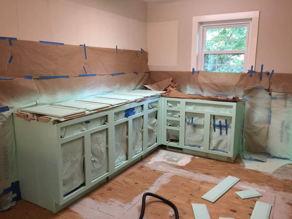 masked kitchen cabinets and painted with overspray showing.