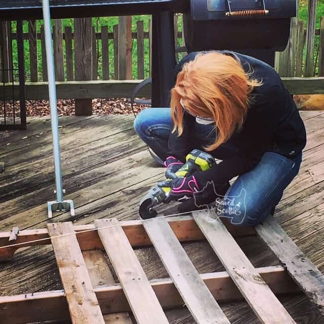 a lady with red hair using an 18V  ryobi job plus cut off tool to cut a wood pallet along a string line.
