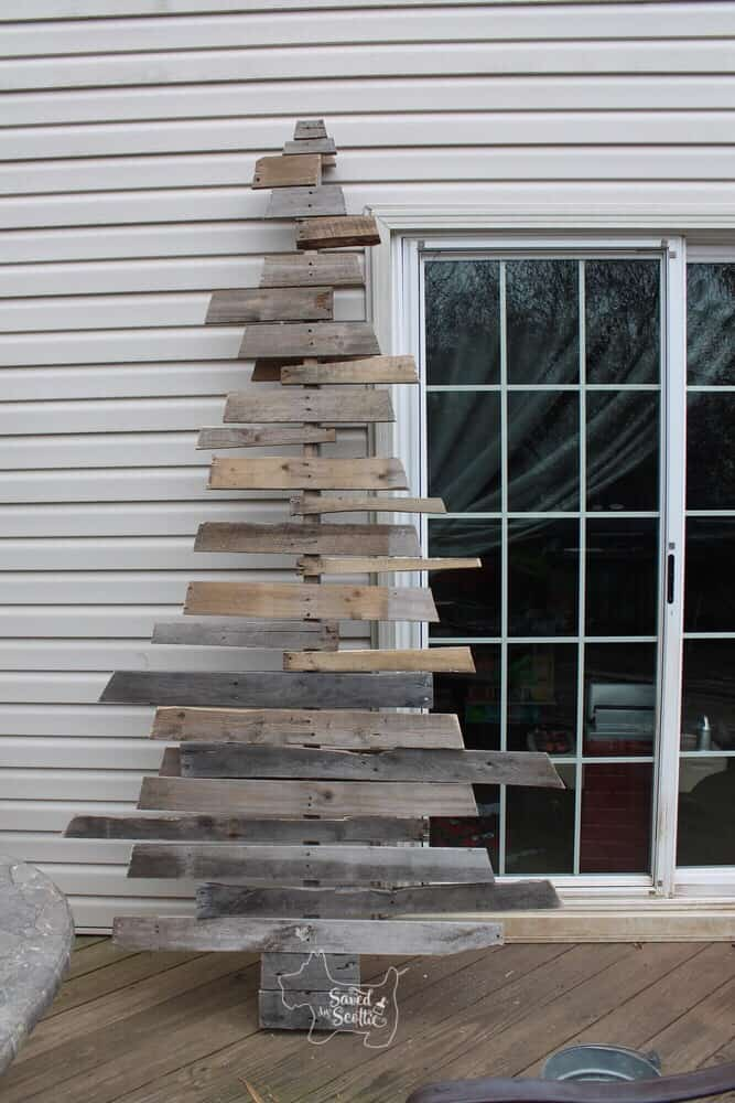 a finished version of a wood pallet christmas tree that is full and randomly uneven on the sides leaning against the siding on a house next to a glass sliding door.
