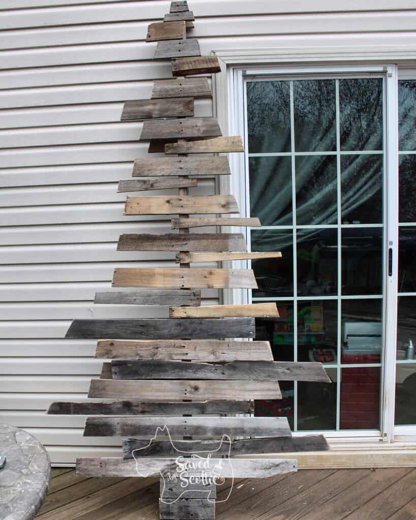 wood pallet christmas tree leaning against the siding of a house next to a sliding glass door and on a wood deck.