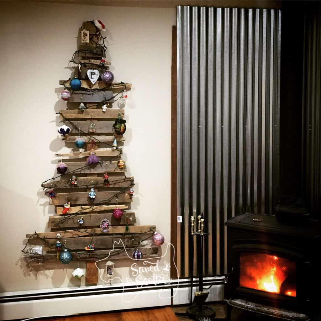 a decorated wood pallet christmas tree with lights off hung on a wall next to a wood stove and corrugated metal backdrop.