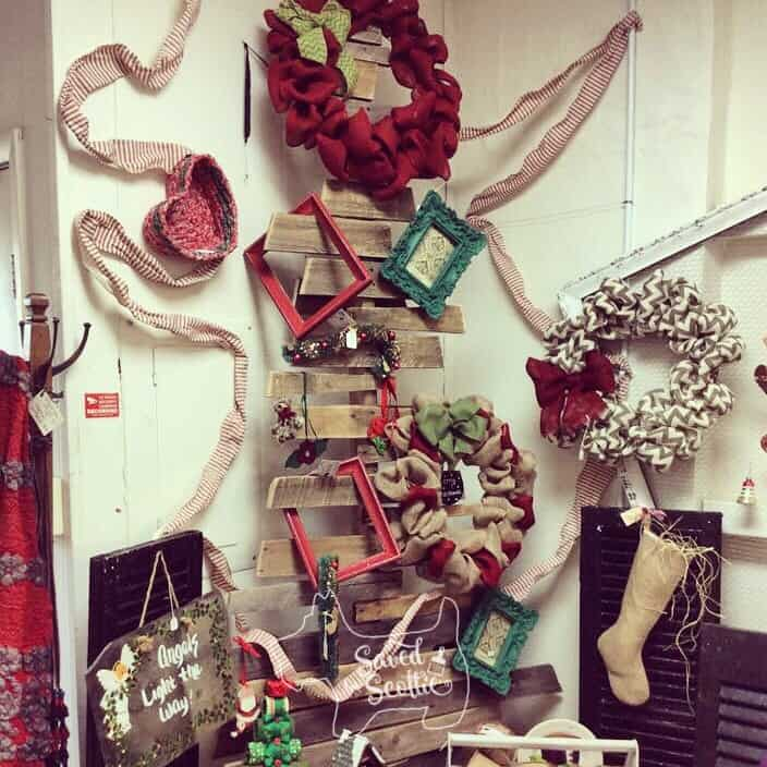 the wood pallet christmas tree on display in a store with ribbon, frames, wreaths, stockings and other decor arranged on it.