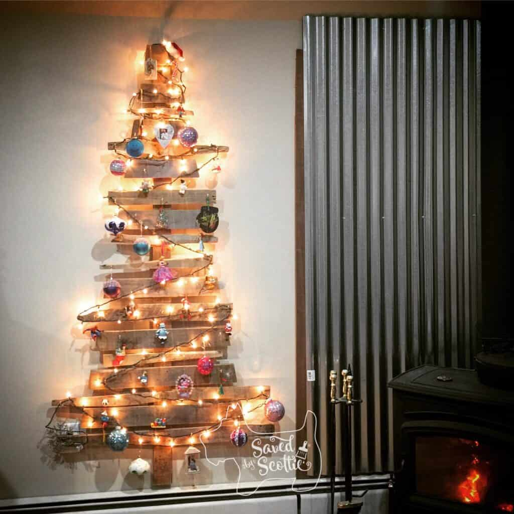 a decorated wood pallet christmas tree with lights on hung on a wall next to a wood stove and corrugated metal backdrop.