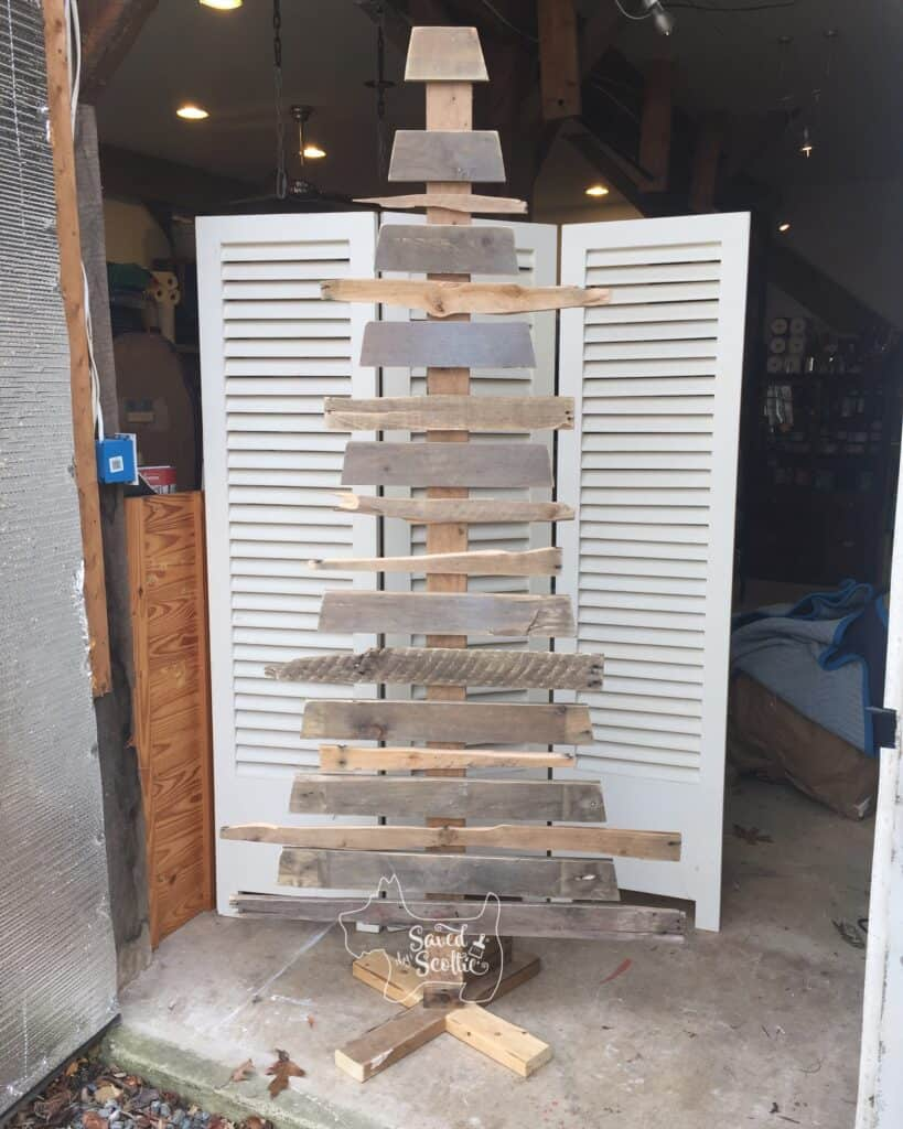 a standing wood pallet christmas tree with white shutter background