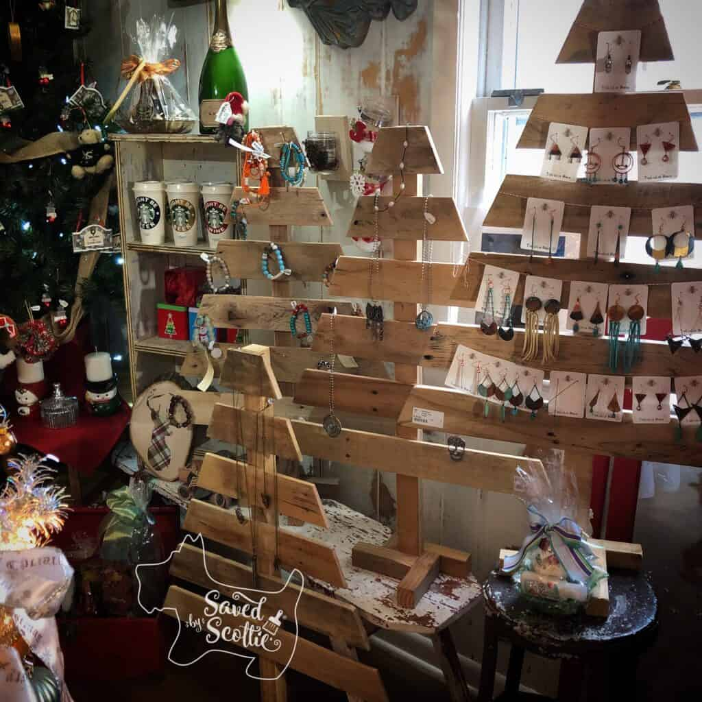 several small wood pallet christmas tree in a shop on display with jewelry for sale arranged on them.