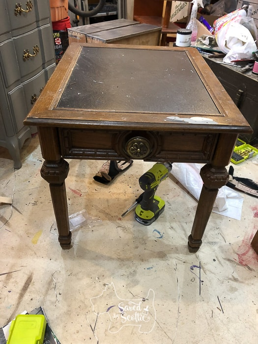 old sad side table with dated floral knob in workshop setting
