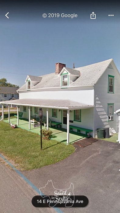 two story white house with large porch spanning the entire width of the house. All windows are trimmed in forest green and porch is covered with green astroturf with long green benches and a green porch swing in the porch area.