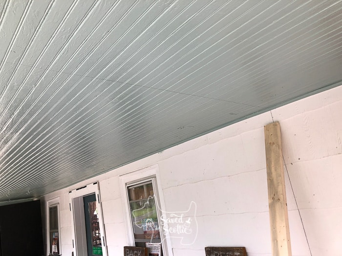 porch ceiling and 2x4 leaning against a white siding wall.