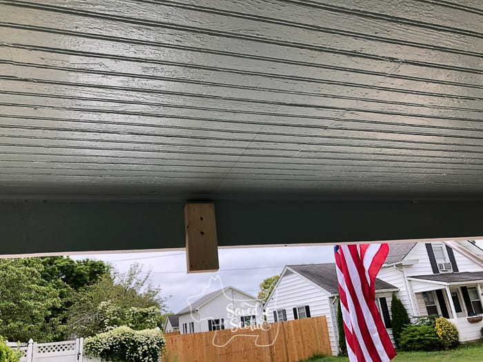 porch ceiling with flag in background small 2x4 scrap screwed into porch overhang as an extra pair of hands to hold a 2x4 beam