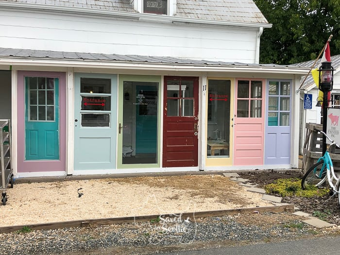 front view of DIY sunroom made from brightly colored vintage doors with bicycle mailbox and pea gravel lawn