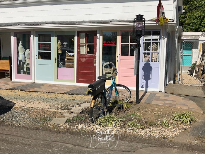 front view of DIY sunroom made from brightly colored vintage doors and stone walkway with bicycle mailbox and pea gravel lawn