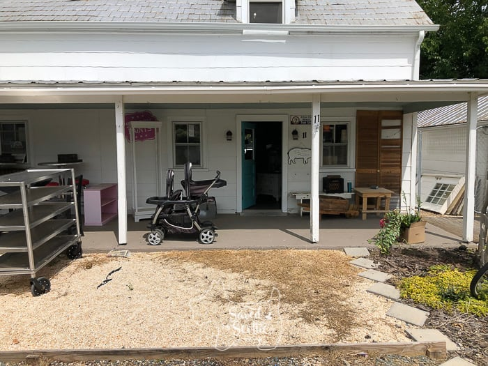 front porch of retail business with bakery rack to the left and abandoned stroller. pea gravel yard with dead weeds are in front of the porch.