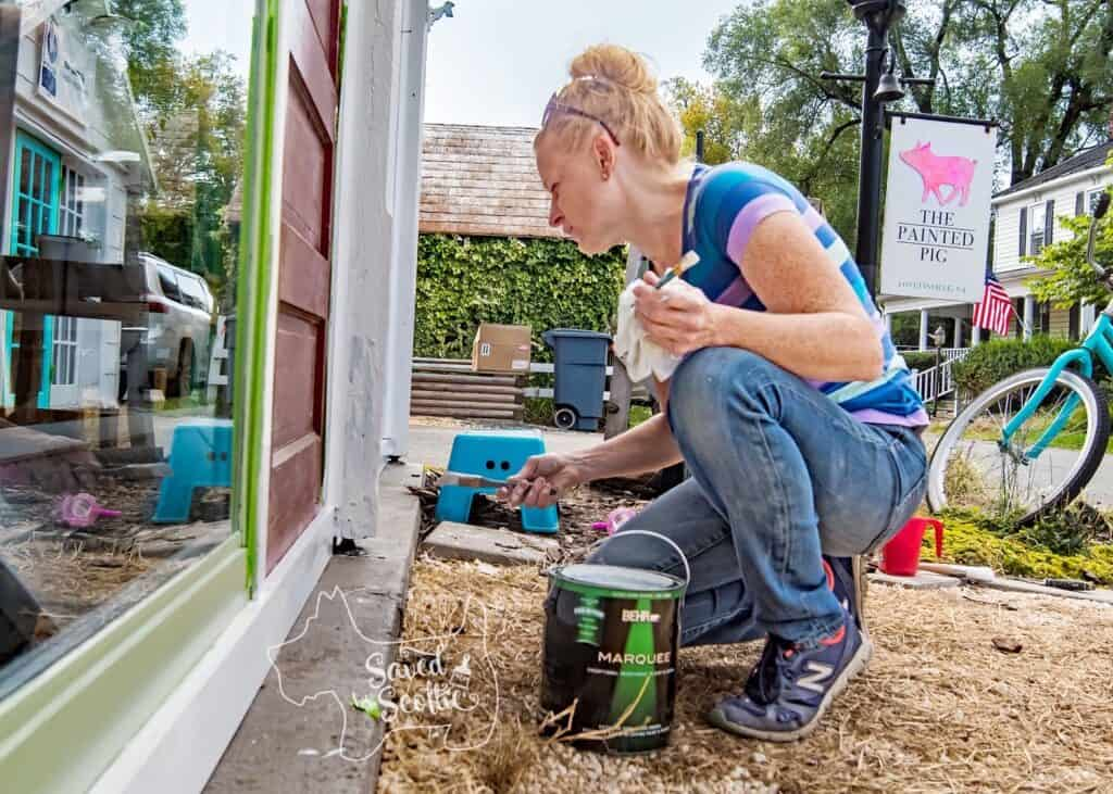 a lady wearing a colorful striped shirt, jeans, and blue athletic shoes, painting doors of a diy sunroom with a can of Behr marquee paint in front of her.