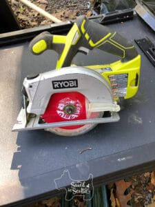 ryobi battery powered circular saw with red diablo blade on black table with leaves
