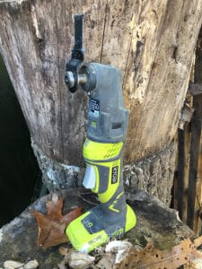 ryobi job plus oscillating saw standing on log with leaves