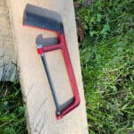 small red hacksaw lying on an oak board in the grass and clover
