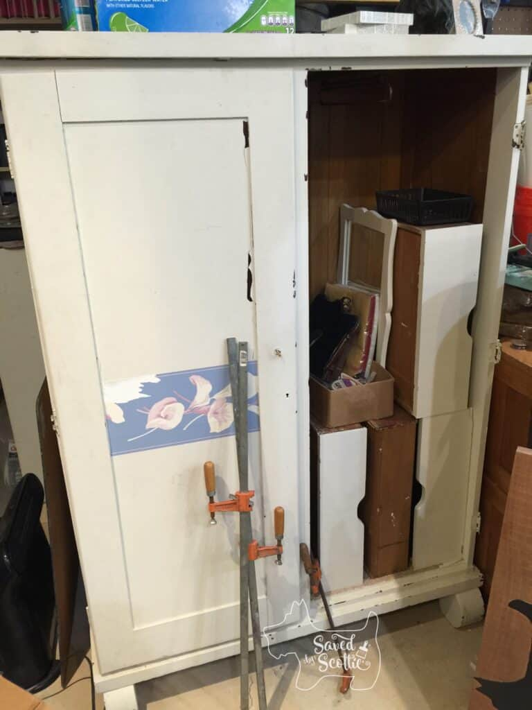an old armoire with a broken door on the right side. Covered in chipping paint and wallpaper border. The open side is full of the drawers and a mirror. Two long clamps are leaning against the front of the armoire