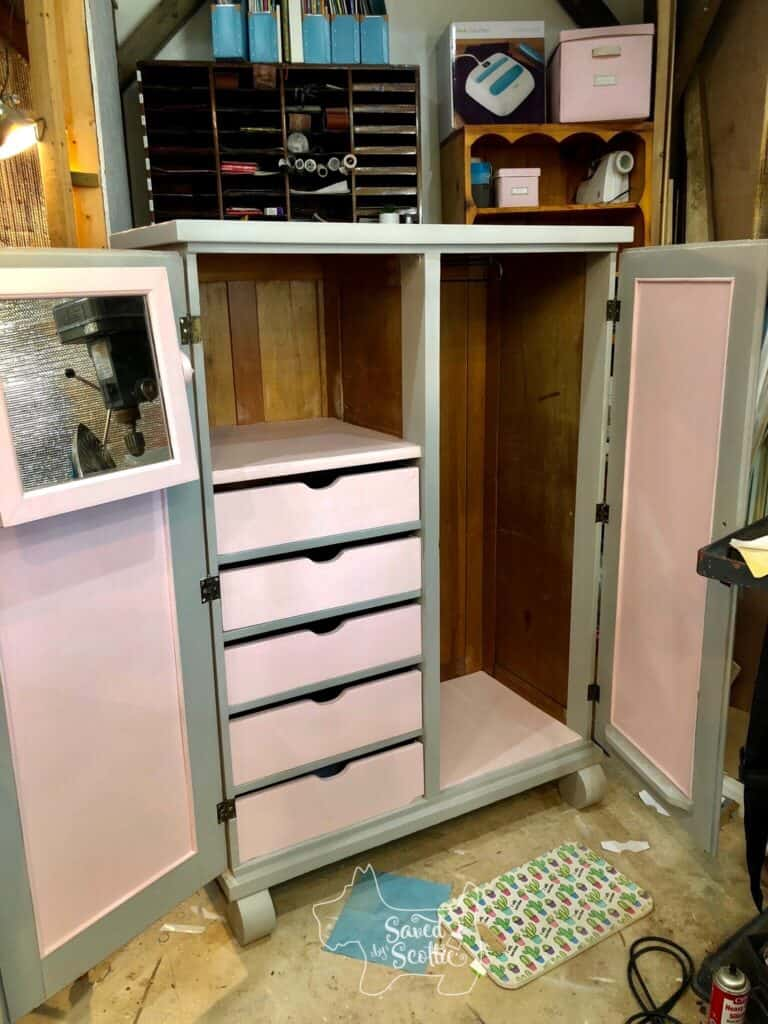 armoire in workshop space open to who the pink painted interior with wood accent walls and gray trim. on the floor in front of it is a kneeling pad and paper shop cloth.