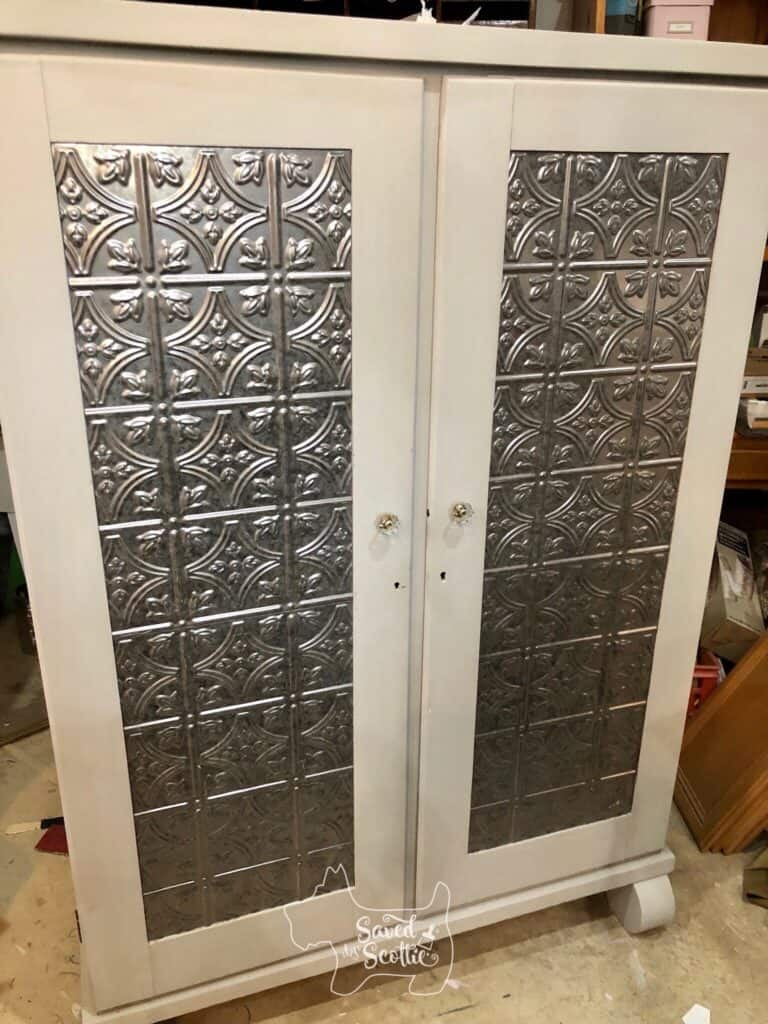 front of closed and finished armoire. body is painted gray and the inset panels of the doors are fasäde decorative panels in a silver metallic that is designed to look like tin ceiling panels.