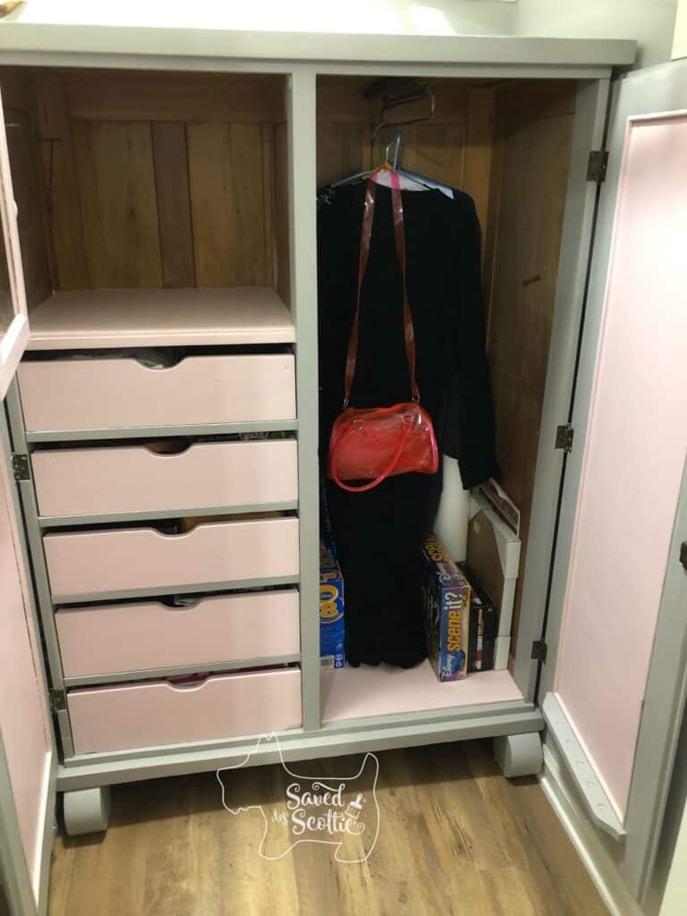 open armoire with pink and gray interior and filled with the possessions of a young adult female
