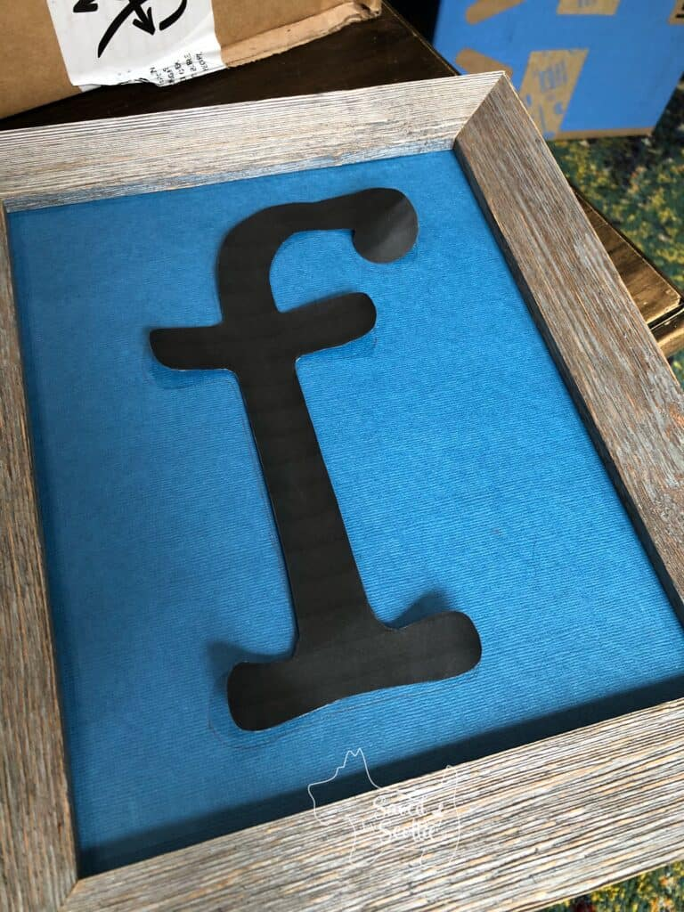 blue piece of scrap book paper in a wood frame with a cut out letter f laying on it
