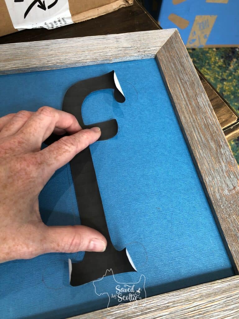 fingers pressing down a cut out letter f on blue scrapbook paper