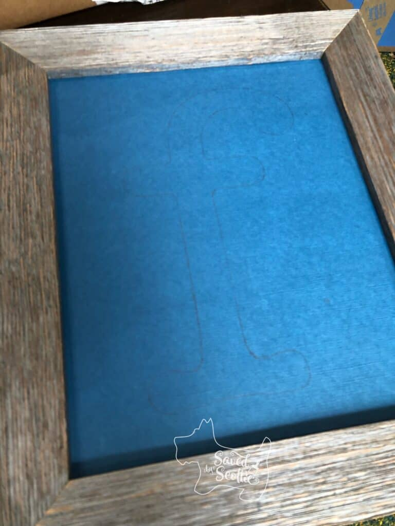 letter f outlined in pencil on blue scrapbook paper inserted in a wood frame.