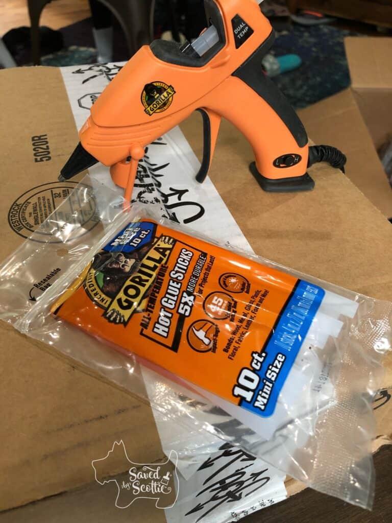 orange glue gun with mini glue sticks from gorilla glue on top of a cardboard box.