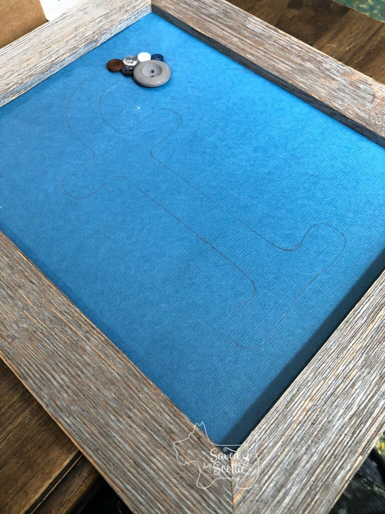 blue scrap book paper placed in wood frame with buttons glued onto the start of the letter f