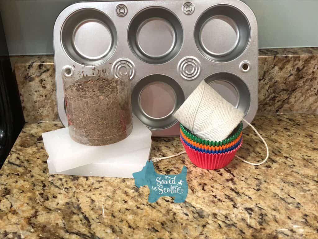 supplies needed for diy firestarters muffin tin, wood shavings, paraffin wax, cupcake liners and cotton string, arranged on a granite countertop