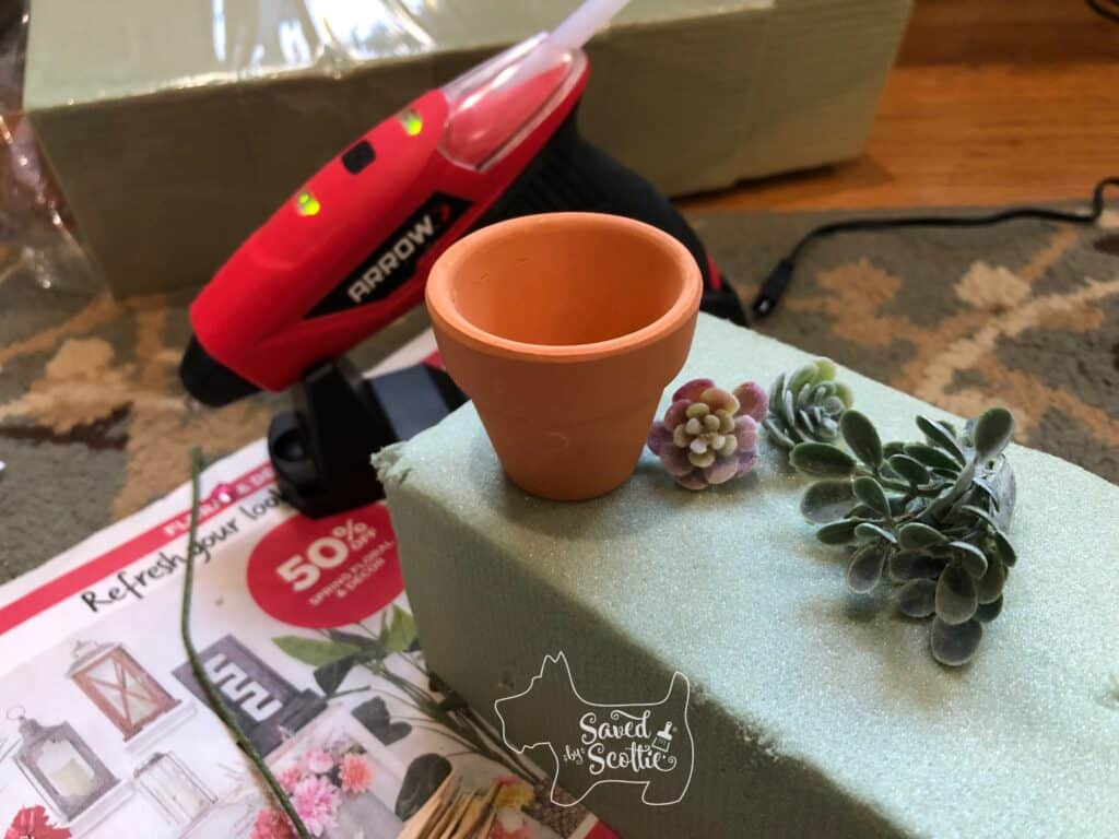 a cordless glue gun with a block of wrapped floral foam in the background. a small terracotta pot and faux succulent buds on top of a block of floral foam laying on a colorful newspaper ad in the foreground