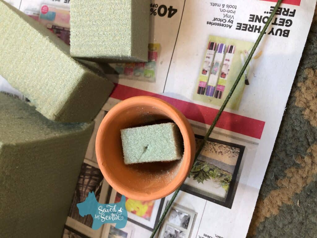 a small terracotta pot with piece of floral foam inserted inside next to blocks of cut floral foam on top of a colorful newspaper ad