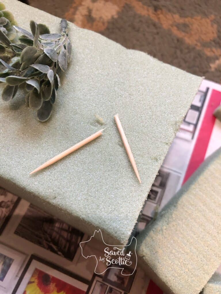 two pieces of a broken toothpick and a small faux succulent bud on top of a block or green floral foam over a colorful newspaper ad